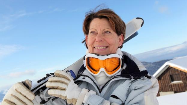 Seniorin mit geschulterten Skis.