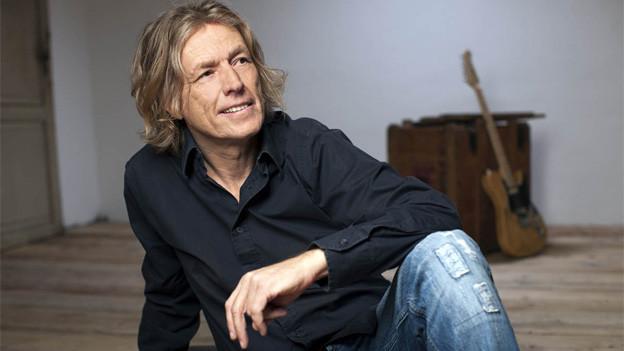 Der Sänger und Musiker sitzt in einem karg eingerichteten Raum auf dem Fussboden.