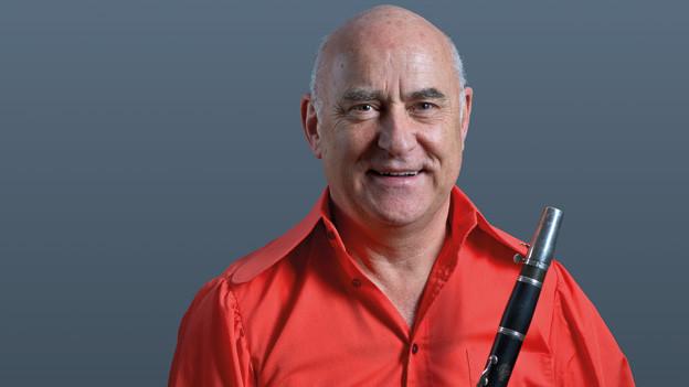 Der Musiker trägt ein rotes Hemd und hält seine schwarze Klarinette in den Händen.