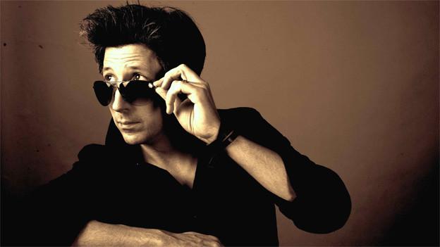 Der Sänger hebt mit der linken Hand seine Sonnenbrille und blickt in die Ferne.