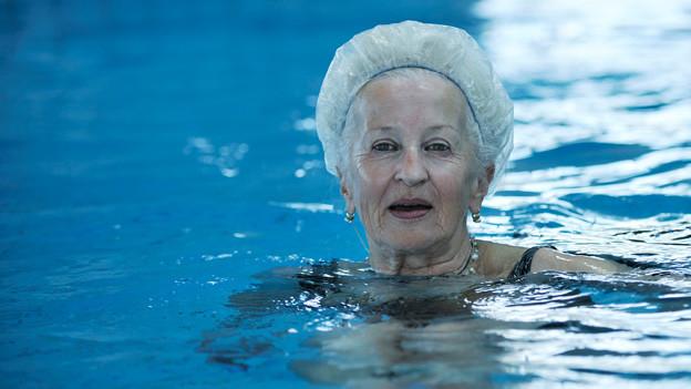 Eine Rentnerin mit Badekappe steht in einem Wasserbecken.
