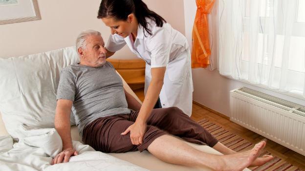 Eine Pflegerin hilft einem Senior aus dem Bett