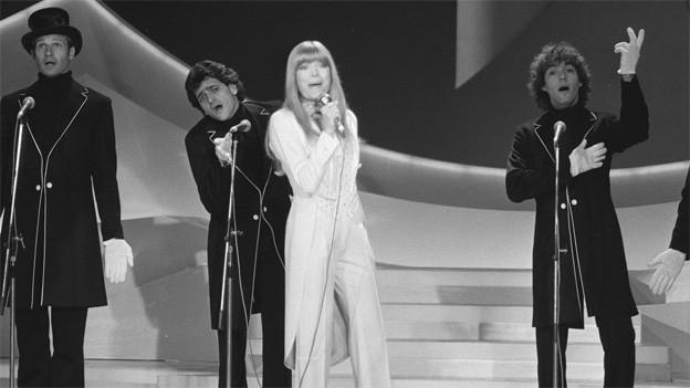 Die Sängerin im weissen Frack und drei Sänger im schwarzen Frack während eines Auftritts.