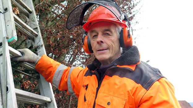 Ein Rentner in Schutzkleidung und mit Helm vor einer Leiter stehend, die an einen Baum angelehnt ist.