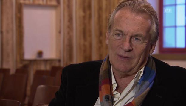 Pepe Lienhard auf einem Konzertstuhl mit weissem Hemd, dunkler West und farbigem Schal.