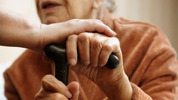 Hand einer jungen Frau auf den Händen einer alten Frau, die sich auf einen Stock abstützt.