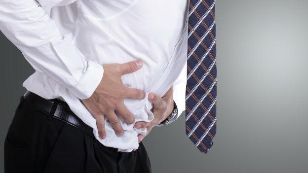 Mann hält seinen Bauch