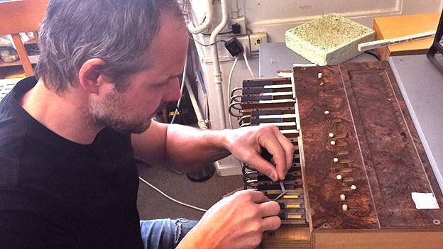 Schmidig repariert ein Schwyzerörgeli auf einem speziellen Tisch.