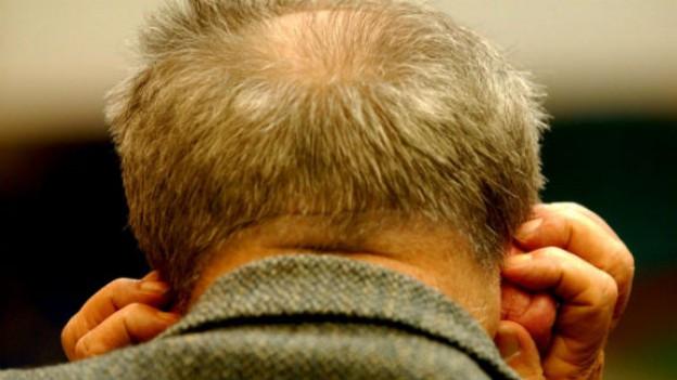 Senior hält sich schmerzhaft die Ohren zu.