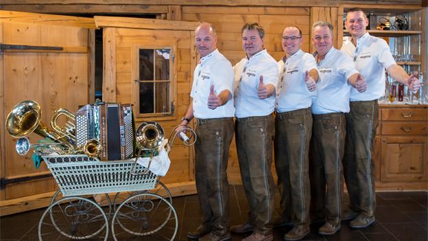 Die fünf Musikanten stehen hintereinander in einer Reihe, vor sich ein alter Kinderwagen gefüllt mit verschiedenen Instrumenten.