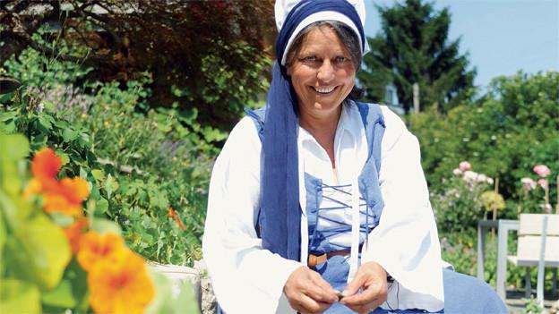 Die Frau trägt blau-weisse Kleider und sitzt in einem blühenden Garten.