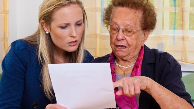 Grossmutter und Enkelin lesen sich ein Testament durch und sind erstaunt.