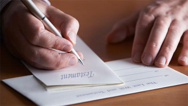 Zwei Hände und ein Kugelschreiber über einen Blatt Papier, auf dem «Testament» steht.