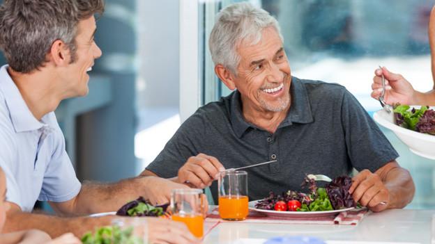 Verschiedene Generationen einer Familie sitzen fröhlich an einem Tisch und geniessen einen Teller Salat.