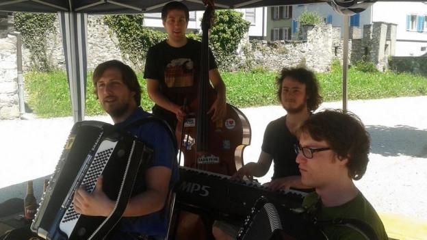 Die vier Musikanten unter einem Zeltdach bei einem Auftritt an einem sommerlichen Tag.