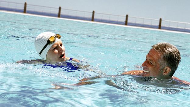 Eine Frau mit Badekappe und Taucherbrille schwimmend neben einem ebenfalls schwimmenden Mann in einem Pool.