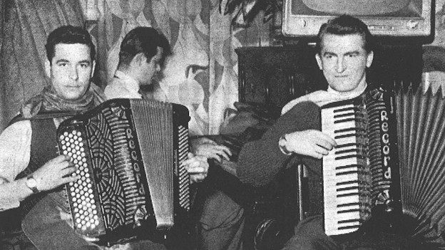 Schwarz-Weiss Fotografie mit einer Volksmusik-Formation in einem Wirtshaus.