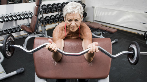 Ältere Frau im Fitnessstudio mit Langhantel.