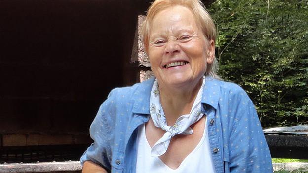 Die Seniorin trägt eine hellblaue Bluse über einem weissen T-Shirt und strahlt an einem sonnigen Tag mit der Sonne um die Wette.