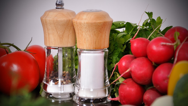 Eine Pfeffer- und eine Salzmühle vor Tomaten und Radieschen.