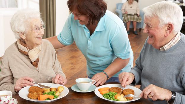 Eine ältere Frau und ein älterer Mann geniessen eine Mahlzeit, während eine Betreuungsperson sie nach ihrem Befinden fragt.