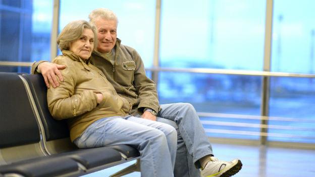 Ein älteres Ehepaar sitzt nebeneinander in der Halle eines Flughafens.