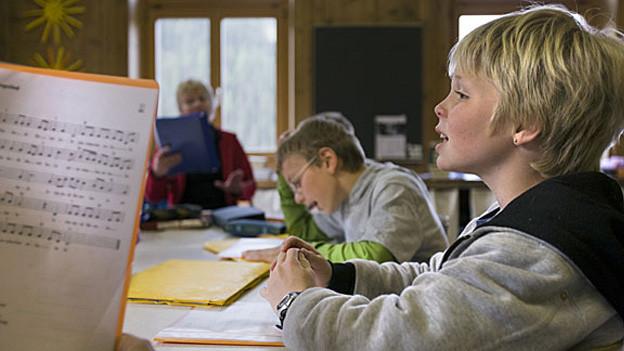 Ein Schüler sitzt am Pult vor einem Notenblatt.