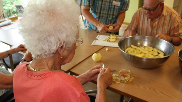 Seniorinnen und Senioren sitzen an einem Tisch und rüsten Äpfel.