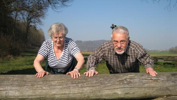Senioren machen Übung an einem Baumstamm.