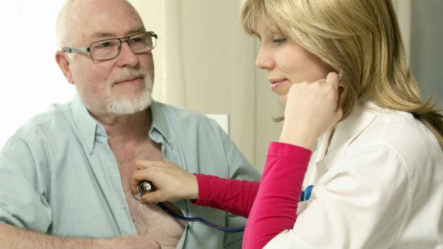 Eine Ärztin hält ihr Stetoskop an die Brust eines älteren Mannes.
