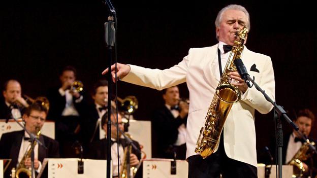 Der Bandleader im weissen Jacket spielt leidenschaftlich Saxophon.