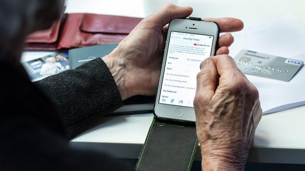 Kursteilnehmerin bestellt per Smartphone ein Billet.