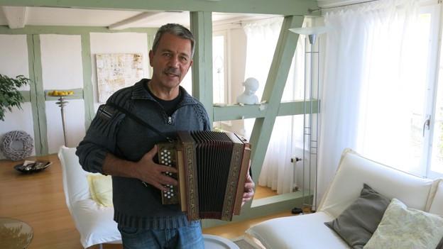 Der Schwyzerörgeli steht mit seinem Instrument in einem Wohnzimmer.