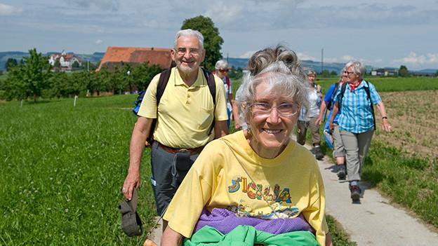 Eine Gruppe von älteren Frauen und Männern, die zufrieden über einen Feldweg spazieren.