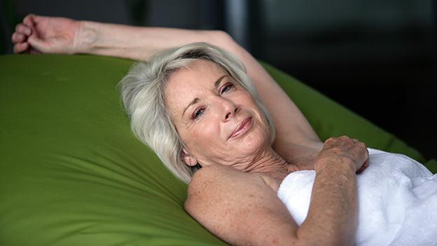 Eine Frau mit weissem Handtuch liegt auf einem grünen Sofa.