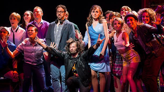 Gruppenbild von Schauspielerinnen und Schauspieler im farbigen Bühnenlicht.
