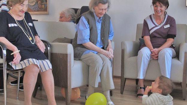 Seniorinnen freuen sich über Baby auf Boden.