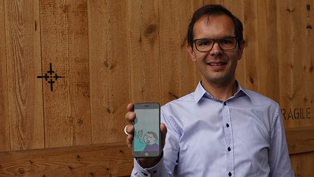 Marco Deplazes steht vor einer grossen Holzkiste und hält sein Smartphone Richtung Kamera.