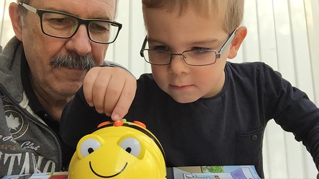 Grossvater und Enkel am Tisch, auf dem ein gelber Kopf eines lachenden Spiel-Roboters steht.