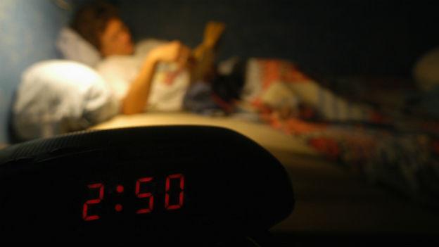 Frau (unscharf) liest im Bett, mitten in der Nacht.