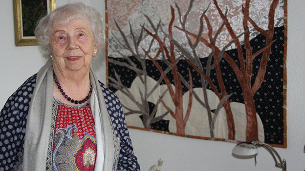 Die Seniorin steht in ihrem Wohnzimmer vor einem Stoffbild, das eine Winterlandschaft zeigt.