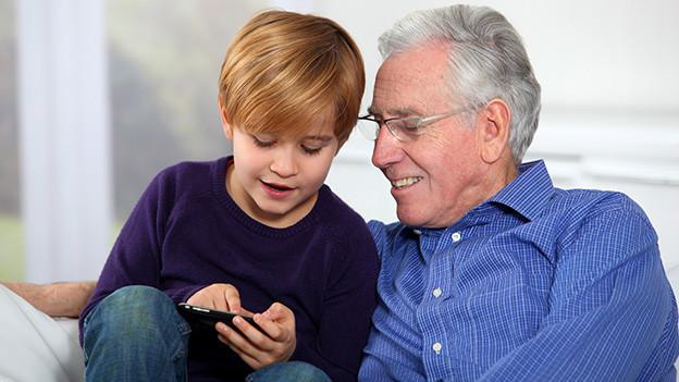 Ein Bub erklärt seinem Vater ein Spiel auf dem Smartphone.