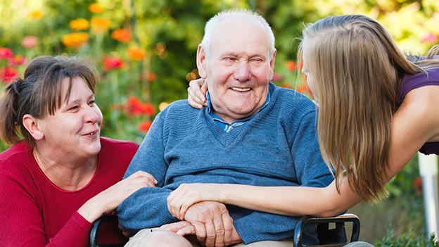 Ein alter Mann sitzt in einem Rollstuhl, rechts von ihm kniet eine Frau, links von ihm steht eine jüngere Frau.