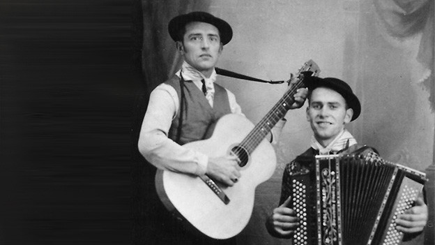 Schwarz-Weiss-Fotografie mit dem Gitarristen und Akkordeonisten.