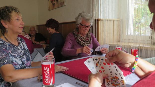 Rund um einen Tisch sitzen vier Frauen, die miteinander jassen.