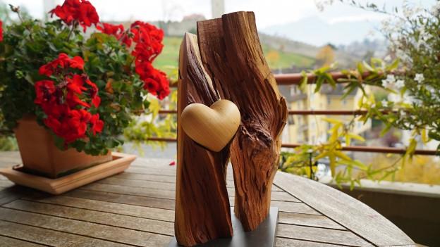 Skultpur aus Holz mit Herz umrahmt von Ästen.