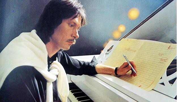 Der Komponist sitzt an einem Flügel und schreibt Noten auf ein Notenblatt.