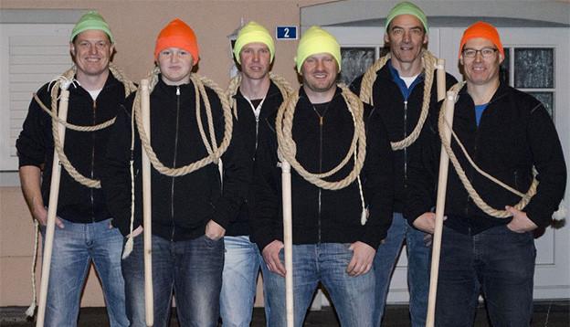 Gruppenbild mit sechs Männern, die ein dickes Seil um den Hals tragen.