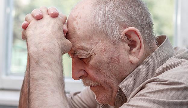 Ein alter Mann sitzt deprimiert an einem Tisch.