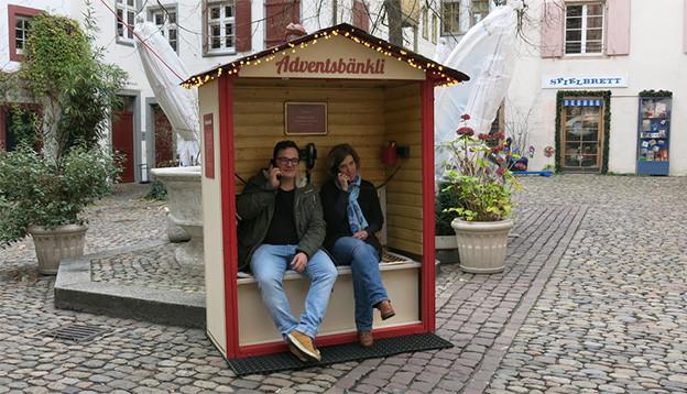 Zwei Personen sitzen auf einer Bank in einer kleinen Holzhütte und halten sich einen Telefonhörer ans Ohr.